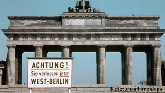 A sign is placed in front of the large stone Brandenburg Gate.