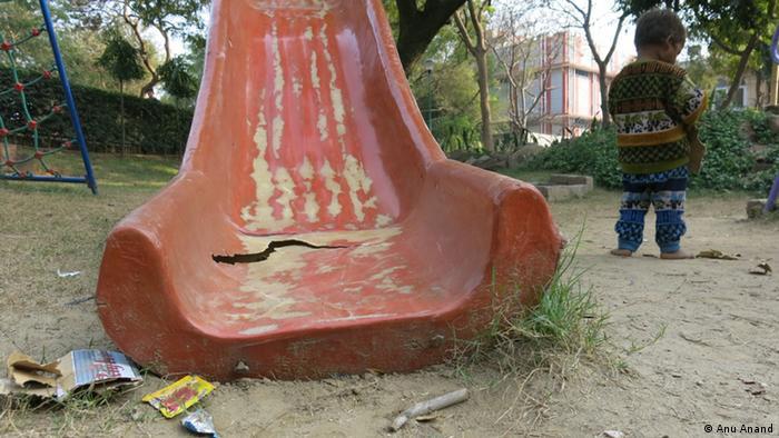 A broken slide on a rundown city playground