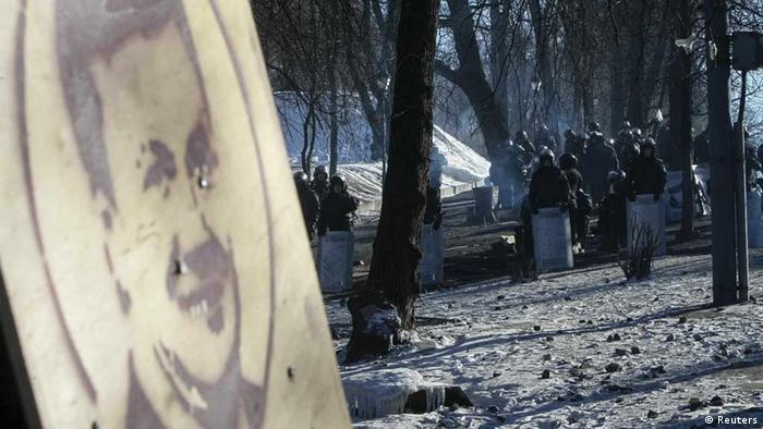 Yanukovych poster, riot police in background (photo: Reuters)