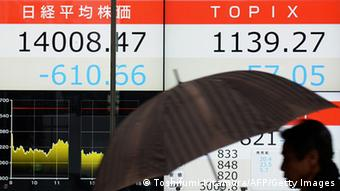 A pedestrian walks past an electronic stock display at the window of the security company in Tokyo on February 4, 2014. Japan's Nikkei index closed down 4.18 percent at 14,008.47 points. AFP PHOTO / TOSHIFUMI KITAMURA (Photo credit should read TOSHIFUMI KITAMURA/AFP/Getty Images)