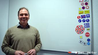 Driving instructor Klaus Hemman stands in front of a whiteboard with various traffic sign magnets Photo: DW / L. Herber