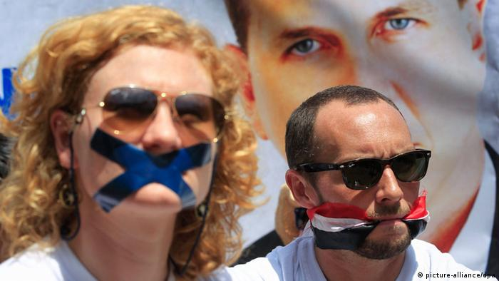 Protesters, with their mouths coverd with tape or bound by an Egyptian kerchief protest Egypt's detention of journalists.