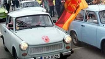 East German Trabant cars pass spectators during a procession