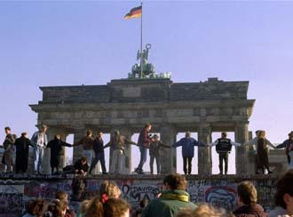 People dancing atop the Berlin Wall in November 1989