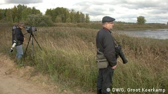 Russian bird watchers wait for birds beside a lake outside of Moscow