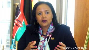A portrait picture of Amina Mohamed standing in front of Kenya's black, red and green flag