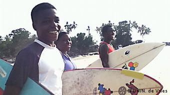3 young surfers with their boards on their way to the sea