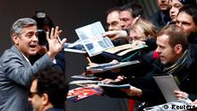 Cast member George Clooney signs autographs before a photocall to promote the movie The Monuments Men during the 64th Berlinale International Film Festival in Berlin February 8, 2014. REUTERS/Tobias Schwarz (GERMANY - Tags: ENTERTAINMENT)