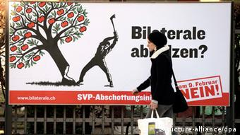 A woman walks next a political poster showinga tree being axed down.