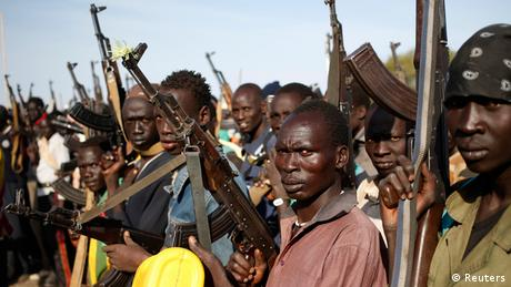 Fighters in Obernil in South Sudan hold guns in the air.