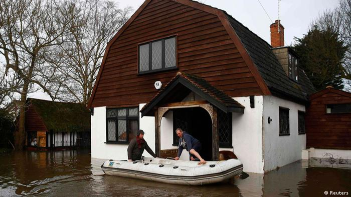 Resident Brian Eves (R) is rescued from his house after the river Thames flooded the village of Wraysbury, southern England February 10, 2014. (Photo via REUTERS/Eddie Keogh)