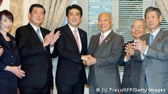 Newly appointed Tokyo Governor Yoichi Masuzoe (3rd-R) shakes hands with Japanese Prime Minister Shinzo Abe (3rd-L) while ruling Liberal Democratic Party (LDP) executives clap their hands at the National Diet in Tokyo on February 10, 2014 one day after Masuzoe won the Tokyo gubernatorial election.