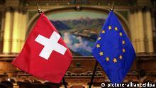 ARCHIV - Fähnchen der EU und der Schweiz im Nationalratssaal in Bern, aufgenommen am 18.05.2000. Die Schweizer haben sich in einer Volksabstimmung überraschend dafür ausgesprochen, die Zuwanderung aus der EU zu begrenzen. Mit 50,3 Prozent fiel die Zustimmung für die Initiative der national-konservativen Schweizer Volkspartei (SVP) «Gegen Masseneinwanderung» am Sonntag denkbar knapp aus. KEYSTONE/Michael Stahl/dpa (zu dpa Experte erwartet keine innenpolitische Krise nach Volksinitiative vom 10.02.2014) +++(c) dpa - Bildfunk+++