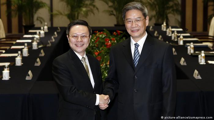 Zhang Zhijun (R), head of the State Council Taiwan Affairs Office, shakes hands with Wang Yu-chi, Taiwan's mainland affairs chief, before their formal meeting, in Nanjing, capital of east China's Jiangsu Province, Feb. 11, 2014.