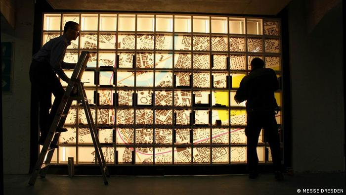 A silhouetted photo of men standing in front of light boxes, which make up the 'Slaughterhouse-Five' memorial wall, which features Vonnegut's personal experience and the scale of Dresden's destruction Photo: Messe Dresden