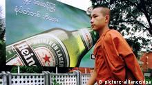 Ein junger buddhistischer Mönch geht am 23.5.1996 an einer großen Reklametafel in Rangun vorbei, auf der für Heineken Bier geworben wird. Seit der Öffnung des birmesischen Marktes werben seit etwa zwei Monaten führende internationale Brauereien mit Großplakaten für ihre Biersorten.