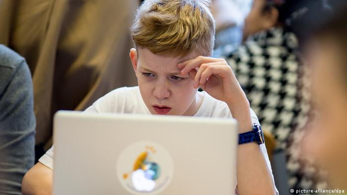 A teenage boy staring at a laptop - Safer Internet Day (picture-alliance/dpa)