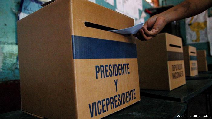 Foto de una persona que coloca su voto en una urna electoral