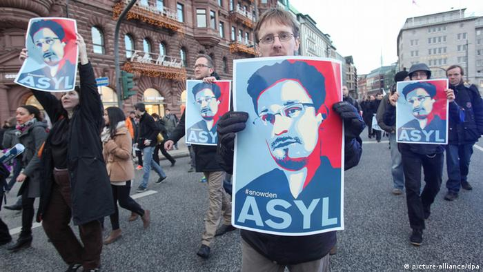 People demonstrate with Snowden Asyl Posters (Foto: Britta Pedersen/dpa)
