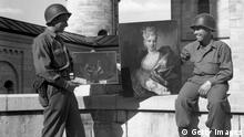 1945: A couple of American soldiers with two of the valuable paintings found amongst a huge cache of art treasures in Neuschwanstein Castle, Fussen, Germany. The paintings were stolen by the Nazis from private collections in Europe during the Second World War. (Photo by Horace Abrahams/Keystone/Getty Images)