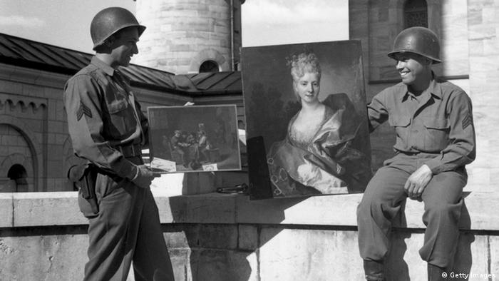 Black-and-white photo of two American soldiers with a painting found in Neuschwanstein in 1945