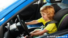 Symbolbild Kind am Steuer Auto Lenkrad Kindersitz