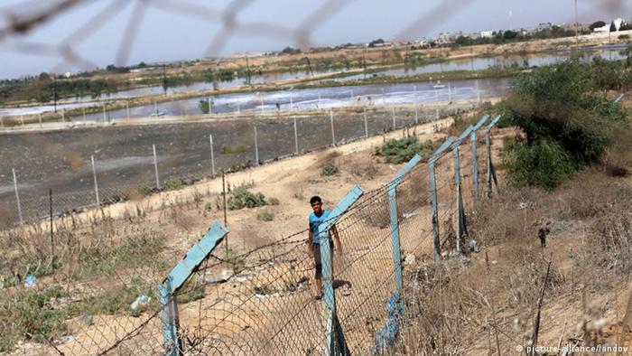 Ein junger Palästinenser geht neben einer Abwasseranlage im Gazastreifen spazieren (Foto: picture-alliance)