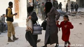 Women walk at a damaged site after an air strike in Aleppo (Photo: REUTERS/Hosam Katan)