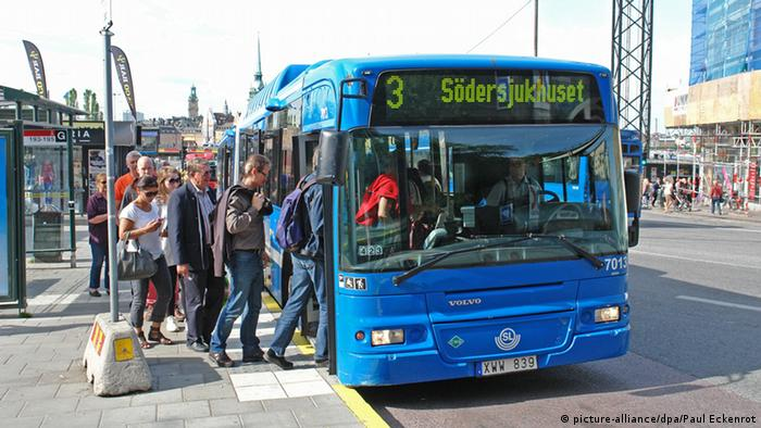 Passengers board an e-bus in Stockholm