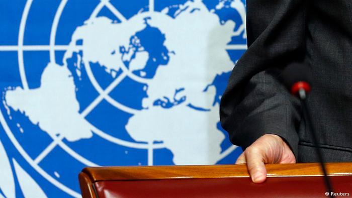 Рука на спинке кресла на фоне логотипа ООН