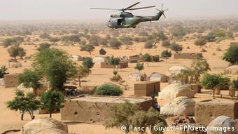 An army helicopter flies over the desert landscape of northern Mali