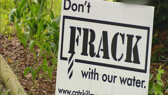 A sign don't Frack with our water stands in a field