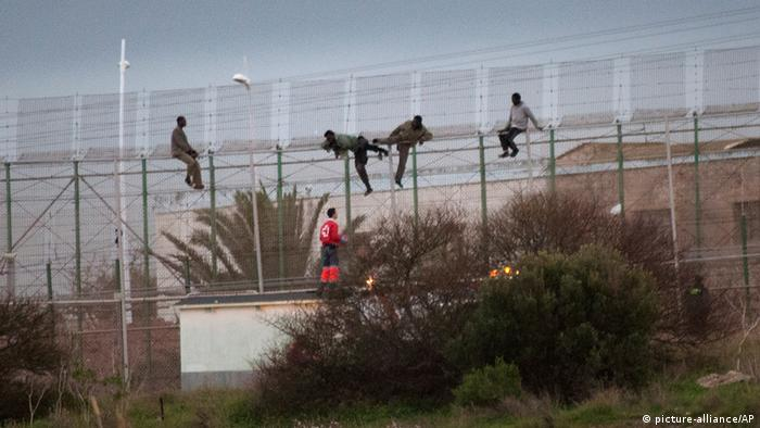 Migrants attempt to climb the barbed wire fence separating Morocco from the Spanish enclave of Melilla