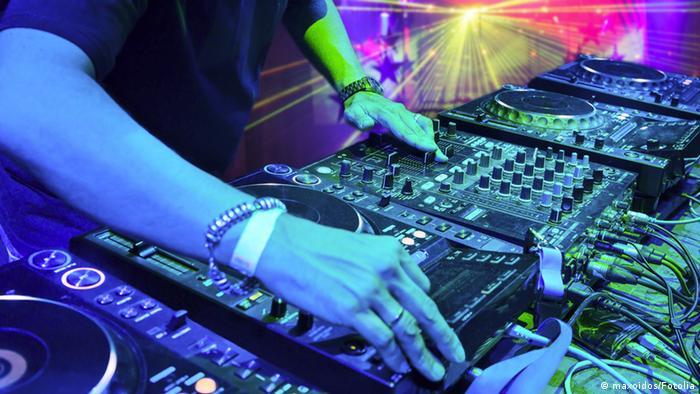 In einer Diskothek bedient ein DJ die Regler des Mischpults