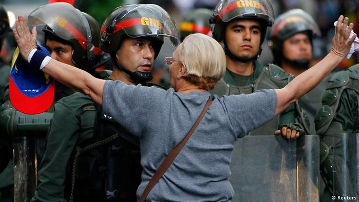 A Venezuelan woman raises her arms in front of a line of security officers wearing helmets.