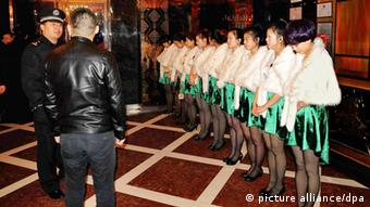 Female Chinese employees stand in line at a sauna during a campaign to crack down on prostitution in Qingdao city, east Chinas Shandong province, 17 February 2014. Thousands of police officers have raided karaoke bars, nightclubs, hotels and saunas in 16 Chinese cities over recent days, detaining more than 1,000 suspects in the latest attempt to curb the countrys illegal but booming sex industry. More busts are likely now that the Chinas Ministry of Public Security ordered a nationwide crackdown on prostitution, gambling and drugs. Some experts doubt the arrests will solve the problem given the popularity of the service in China. Others say the biggest reason that prostitution remains endemic to China is that police and authorities in cities take bribes to overlook the crime, and so the only thing to do is no longer treat it as a crime. Li Yinhe, a sociologist at the Chinese Academy of Social Sciences, says the government must reconsider its laws and approach. Legalizing the industry could reduce corruption and ensure health checks and education of sex workers, who could be offered training for other work, she told Caixin Media. Prostitution is available everywhere in China, from street-side barbershops to high-end hotels. Many of the arrests in the latest sweep are taking place in Dongguan, a southern manufacturing hub long notorious as Chinas sex capital.