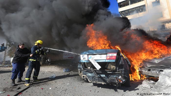 Lebanese firefighters extinguish a burned car at the site of an explosion, in the suburb of Beir Hassan, Beirut. (Photo: AP Photo/Hussein Malla)