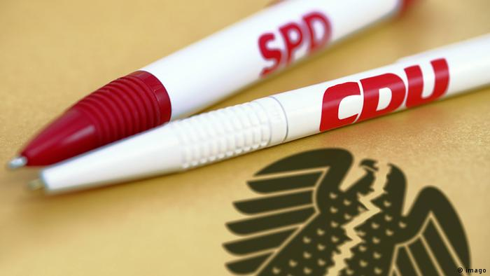Two pens, one with SPD, other with CDU logo, on broken up German eagle (imago)