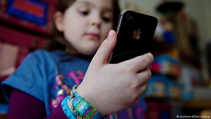 Girl holding smartphone (picture-alliance/dpa)
