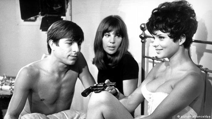 Filmszene aus Zur Sache Schätzchen mit zwei Frauen und einem Mann, nur wenig bekleidet, auf einem alten Bett, die eine Frau hält eine Pistole in der Hand (picture-alliance/dpa)