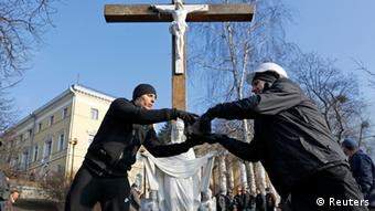 Two men in black stand in front of a cross and a statue of Mary (Photo: Yannis Behrakis/REUTERS)