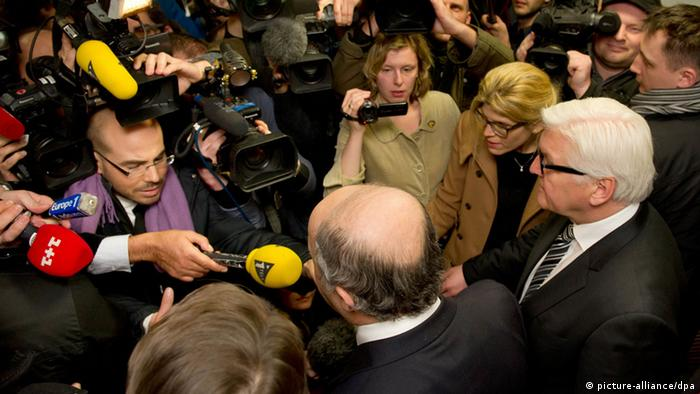 Politicians are surrounded by cameras, microphones and people