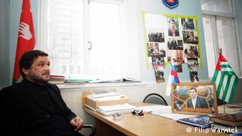Djarnaz Beniya a wrestling coach in Abkhazia sitting in his office with his medals.