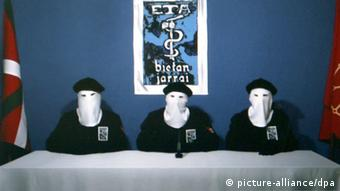 Men wearing white masks over their faces in a room with a blue background.