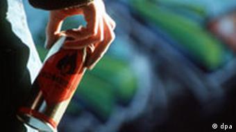 Ein jugendlicher Sprayer steht mit einer Farb-Spraydose, im Jargon als Kanne bezeichnet vor einem Graffiti