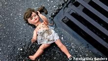 A dirty and disheveled doll lies on the street next to a drainage grate.