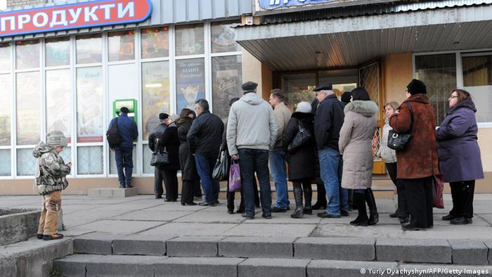 People stand in a queue to get their money from bank machine in the western Ukrainian city of Lviv on February 20, 2014, as a result of the financial panic caused with clashes between anti-government opposition and police in Kiev. AFP PHOTO/ YURIY DYACHYSHYN (Photo credit should read YURIY DYACHYSHYN/AFP/Getty Images)