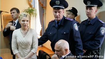 Yulia Tymoshenko in court, surrounded by uniformed officials