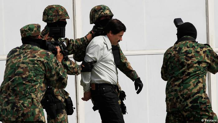 Joaquin Shorty Guzman is escorted by soldiers during a presentation at the Navy's airstrip in Mexico City February 22, 2014. Mexico has captured its most wanted man, drug kingpin Guzman, President Enrique Pena Nieto said via Twitter on Saturday, in a major victory in a long, grisly fight against drug gangs. Guzman, known as El Chapo (Shorty) in Spanish, runs Mexico's infamous Sinaloa Cartel and over the past decade emerged as one of the world's most powerful organized crime bosses. REUTERS/Henry Romero (MEXICO - Tags: CIVIL UNREST CRIME LAW DRUGS SOCIETY MILITARY)