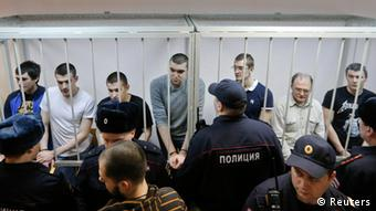 Defendants in the Bolotnaya case stand in a holding cell as they wait for their sentencing in Moscow, February 24, 2014